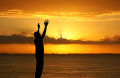 Worship. Man with his hands up watching the sun set Royalty Free Stock Image