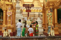 Worship God at Shwedagon, Yangon , Myanmar. A family group, father, mother, girl and boys  respect their god by pouring water  as the traditional ceremony Stock Photos