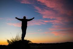 Worship God of Sunset. Man on a hill worshiping the one and only God who created sunset Royalty Free Stock Image