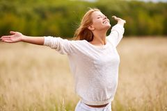 Worship. Happy young female with her arms outstretched enjoying freedom Stock Photo