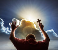 Worship, love and spirituality. Praying man lifts his hands in prayer and holds a cross to heaven with heavenly sunset through a cloudscape concept for religion Royalty Free Stock Photo