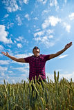 Worship - man in a wheat field. Young strong man standing with arms wide open in wheat field Royalty Free Stock Photos
