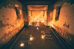 Worship in mysterious church interior with lighting candles and cross. In the night. Church of St. Matthew/Kostel Sv. Matouse royalty free stock photography