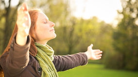 Worship with Open Arms. Woman worshiping with open arms or taking in the Autumn sun in a park Stock Photo