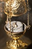 Worship service concept. Incense on burning coal tablet in golden censer emits fragrance smoke rising up. Close-up. Vertical photography with selective focus stock photo