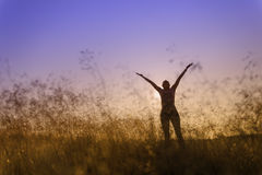 Silhouette of a woman lifting her hands in worship Royalty Free Stock Images