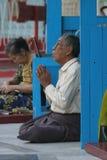 Worship at the swadagon pagoda. Man praying at the swadagon paoda in burma Stock Photo