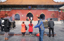 Worshipers holding incense sticks pray at Yonghegong Lama Temple in Beijing Royalty Free Stock Photos