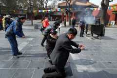 Worshipers holding incense sticks pray at Yonghegong Lama Temple in Beijing Stock Photos