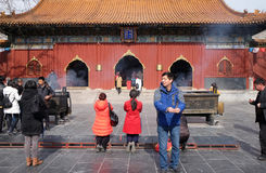 Worshipers holding incense sticks pray at Yonghegong Lama Temple in Beijing Stock Photo