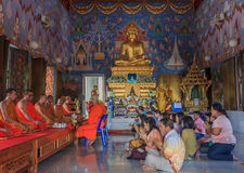 Worshipers and monks praying in Wat Kaew Korawaram Temple Stock Photo
