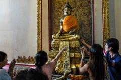 Worshiping and decorating Buddha statue Royalty Free Stock Photography
