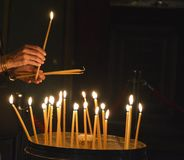 A worshipper lights candles at the Church of the Holy Sepulchre, Jerusalem. Expressions of faith: a worshipper lights votive candles at the Church of the Holy stock image