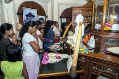 Worshippers ber i framdel av en staty av Lord Buddha inom templet av den sakrala tandreliken Royaltyfri Foto