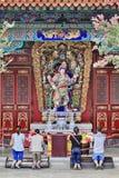 Worshippers framme av ett utsmyckat altare på den Yuantong templet, Kunming, Kina royaltyfri bild