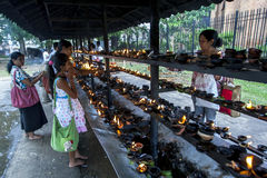 Worshippers light oil lamps within the Temple of the Sacred Tooth Relic in Kandy, Sri Lanka. Worshippers light oil lamps within the Temple of the Sacred Tooth Royalty Free Stock Image