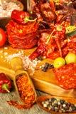 Worst of salami met Spaanse peperpeper met kruiden op houten lijst Kruidige salami met Spaanse peper Ongezond vet voedsel stock afbeelding