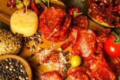 Worst of salami met Spaanse peperpeper met kruiden op houten lijst Kruidige salami met Spaanse peper Ongezond vet voedsel stock fotografie