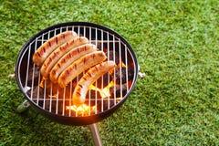 Worsten die op een draagbare barbecue roosteren stock afbeeldingen