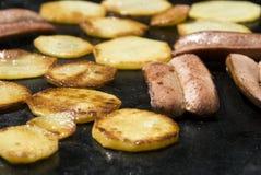 Worsten en aardappels op de barbecue Royalty-vrije Stock Foto's