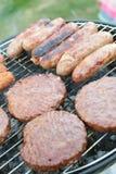 Worsten en burgers op barbecue Stock Fotografie