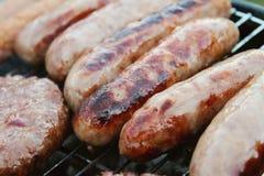 Worsten en burgers op barbecue Royalty-vrije Stock Afbeeldingen