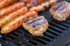 Worsten en Hamburgers bij de Grill royalty-vrije stock afbeelding