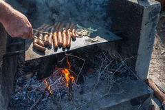 Worsten en uien die over brandbbq koken in Australië stock fotografie