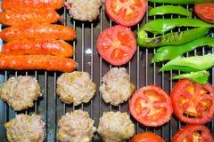 Worsten, gehaktballen, tomaten en capsica in de grill Stock Foto's