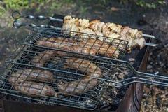 Worsten op de grill en kebab op vleespennen op worden geroosterd die Stock Foto