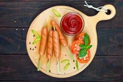 Worsten op vleespennen met ketchup en verse die tomaten, op een rond houten dienblad wordt gediend royalty-vrije stock foto's