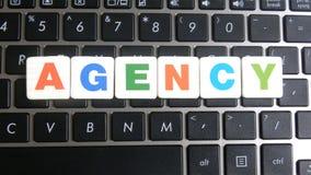 Wort-Agentur auf Tastaturhintergrund Stockbild