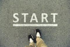 Wort-Anfang geschrieben auf eine Asphaltstraße Draufsicht der Beine und Stockbilder