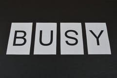 Wort beschäftigt auf schwarzem Hintergrund lizenzfreies stockfoto