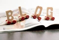 Wort - Blog - auf Rädern auf einer offenen Zeitschrift Stockbild