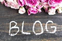Wort-Blog mit rosa Rosen auf einem rustikalen hölzernen Hintergrund Lizenzfreie Stockfotos