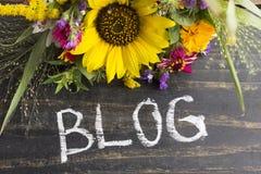 Wort-Blog mit Sommer-Blumen auf einem rustikalen hölzernen Hintergrund Stockfoto