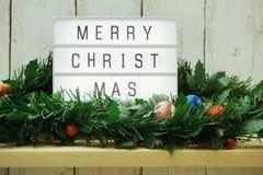 Wort der frohen Weihnachten auf Leuchtkasten mit grüner Lamettadekoration lizenzfreie stockfotos