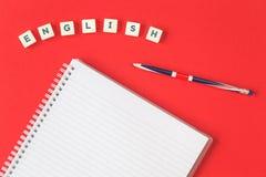 Wort-Englisch ein Bleistift mit angeordnetem Notizblock auf Rot lizenzfreie stockfotos