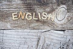 Wort Englisch formulierte mit hölzernen Buchstaben auf einem hölzernen Hintergrund stockfotografie