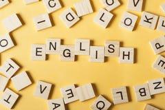 Wort ENGLISCH machte mit h?lzernen Buchstaben des Blockes nahe bei einem Stapel anderen Buchstaben auf Holztisch lizenzfreie stockfotografie