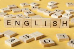 Wort ENGLISCH machte mit h?lzernen Buchstaben des Blockes nahe bei einem Stapel anderen Buchstaben auf Holztisch lizenzfreies stockbild