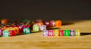 Wort-Englisch von einem Quadrat von farbigen Blöcken auf einer Holzoberfläche stockfotos