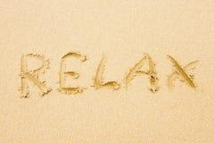 Wort entspannen sich geschrieben auf Sand Lizenzfreies Stockfoto