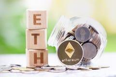 Wort ETH Münzen Ethereum ETH und des hölzernen Blockes auf unscharfem Grünhintergrund stockbilder