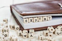 Wort EXPERTE auf altem Holztisch Stockbild