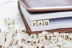 Wort FAQ auf altem Holztisch Stockfoto