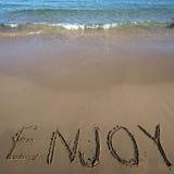 Wort genießen geschrieben auf Sand Stockfotografie