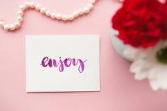 Wort genießen handgeschriebenes in der Kalligraphieart mit Aquarell Blumenzusammensetzung auf einem blassen - rosa Pastellhinterg Lizenzfreies Stockfoto