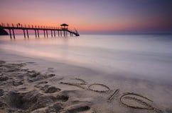 Wort 2016 geschrieben auf Sand und Schattenbild des Fischerhäuschens DU Lizenzfreie Stockfotografie